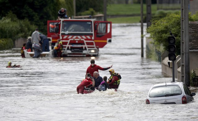 French firefighters on a small boat evacuate residents from a flooded area after heavy rain falls in Chalette-sur-Loing, near Orleans, France, June 1, 2016. (Photo by Christian Hartmann/Reuters)