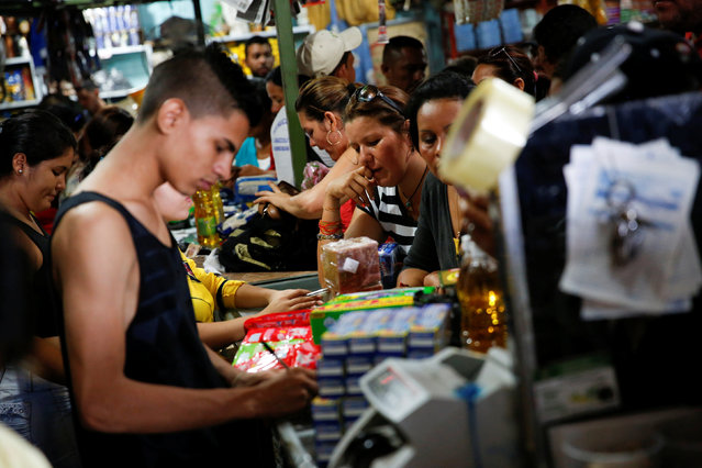 Customers wait to be served at a store that sells food and staple items in Puerto Santander, Colombia, June 3, 2016. (Photo by Carlos Garcia Rawlins/Reuters)