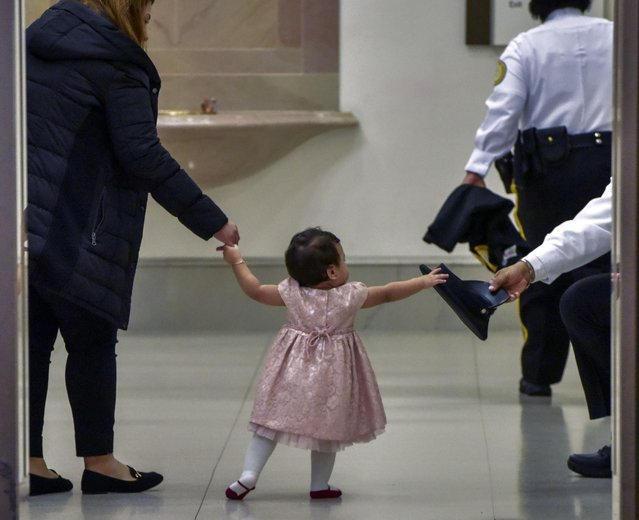 Kimberly Del Cid, 1, center, reaches for the hat of Officer Edward Twine while waiting for her father, Mauricio Del Cid, to be sworn in as a new U.S. citizen in front of the original Declaration of Independence, the Constitution and the Bill of Rights, in the Rotunda of the National Archives in Washington on December 16, 2019. (Photo by Bill O'Leary/The Washington Post)