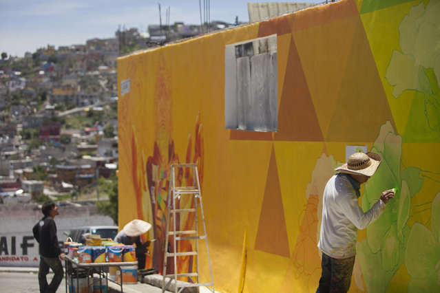 Carlos Duarte, right, of the artist collective German Crew, paints a section of a gigantic mural in the Palmitas neighborhood of Pachuca, Mexico, Thursday, July 30, 2015. (Photo by Sofia Jaramillo/AP Photo)