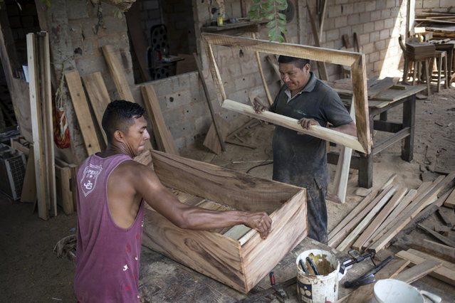 Sergio Morales, right, and Joelvis Cantillo, build a simple coffin at their furniture workshop in Maracaibo, Venezuela, November 20, 2019. Two years ago the carpenters started building coffins for less than $100 instead of furniture due to the high demand for cheaper coffins. (Photo by Rodrigo Abd/AP Photo)