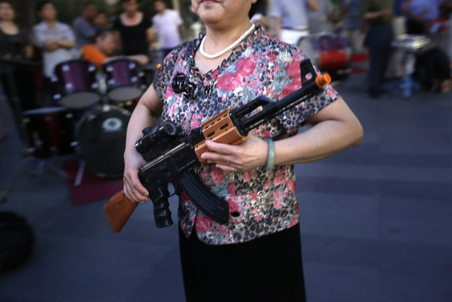 "A local woman holding a toy gun prepares to dance to revolutionary songs as part of her daily exercise at a square outside a shopping mall in Beijing, June 27, 2014. About 30 local residents formed this ""Nanguan"" art group that enjoys performing and dancing to revolutionary songs as part of their nightly fitness activity. (Photo by Jason Lee/Reuters)"