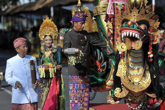 Indonesia President Joko Widodo (C), accompanied by Bali Governor Made Mangku Pastika (L), opens the annual Bali Arts Festival in Denpasar, Bali, Indonesia June 11, 2016. (Photo by Nyoman Budhiana/Reuters/Antara Foto)