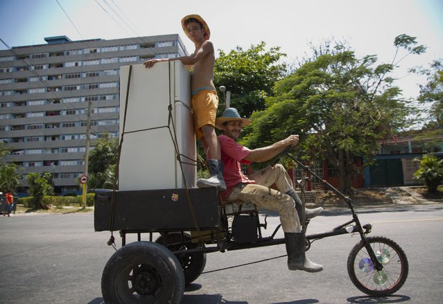A man steers a tricycle carrying a young man as they haul a refrigerator through Havana, Cuba, Friday, April 17, 2015. (Photo by Ramon Espinosa/AP Photo)