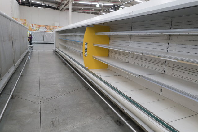 A woman is pictured past empty refrigerator shelves at a Makro supermarket in Caracas August 4, 2015. Venezuelan supermarkets are increasingly being targeted by looters, as swollen lines and prolonged food shortages spark frustration in the OPEC nation struggling with an economic crisis. (Photo by Carlos Garcia Rawlins/Reuters)