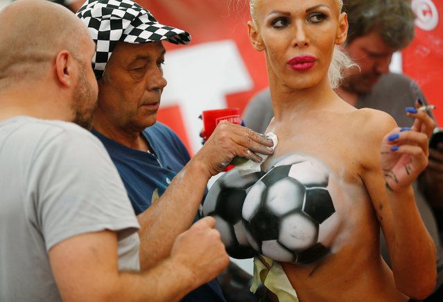 """An erotic model is sprayed with body paint during the promotional event """"Sеxy Soccer"""" of an erotic video website in Berlin, Germany, June 17, 2016. (Photo by Hannibal Hanschke/Reuters)"""