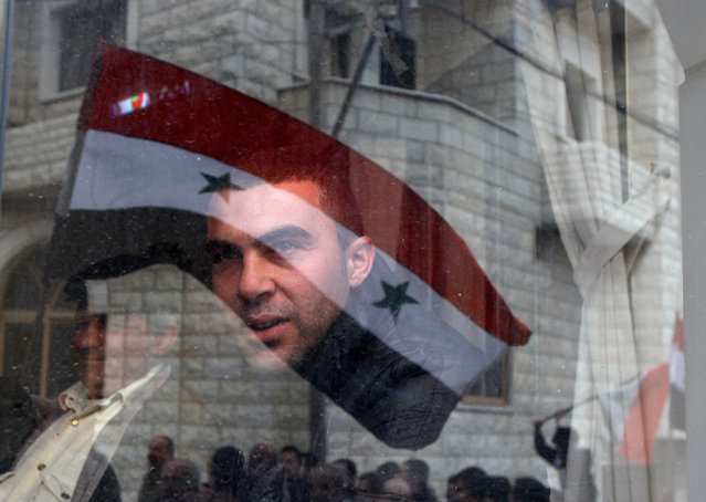 A Syrian flag is reflected on a man watching a rally