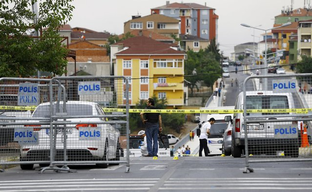 Plainclothes police officers and forensic experts examine the scene after an attack on a police station in Istanbul, Turkey, August 10, 2015. Overnight, a vehicle laden with explosives was used in the attack on the police station in the Istanbul district of Sultanbeyli at around 01:00 on Monday (22:00GMT on Sunday), injuring three police officers and seven civilians, police said. (Photo by Huseyin Aldemir/Reuters)
