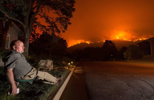 Mike Wright sits in a lawn chair at his home as flames from the Detwiler fire approach the town of Mariposa, California on July 18, 2017. The Detwiler fire is approaching the town of Mariposa and has burned more than 25,000 acres so far. (Photo by Josh Edelson/AFP Photo)