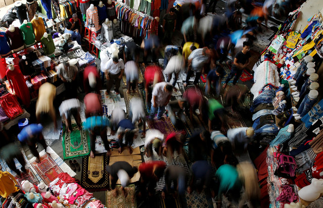 Muslims are seen praying between clothes stalls on Friday prayers during the fasting month of Ramadan at Tanah Abang market in Jakarta, Indonesia, June 24, 2016. (Photo by Reuters/Beawiharta)