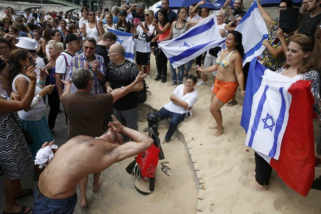 """People gather with Israeli and French flags on a artificial sand beach at """"Paris Plages"""" to show their support  for the """"Tel Aviv on Seine"""" event, in Paris, France, August 13, 2015. (Photo by Pascal Rossignol/Reuters)"""