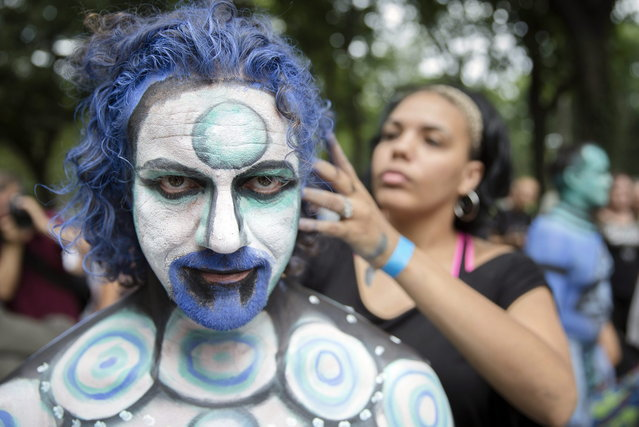 Cully Firmin, of Lafayette, La., is painted at Columbus Circle as body-painting artists gathered to decorate nude models as part of an event featuring artist Andy Golub, Saturday, July 26, 2014, in New York. Golub says New York was the only city in the country that would allow his inaugural Bodypainting Day. (Photo by John Minchillo/AP Photo)