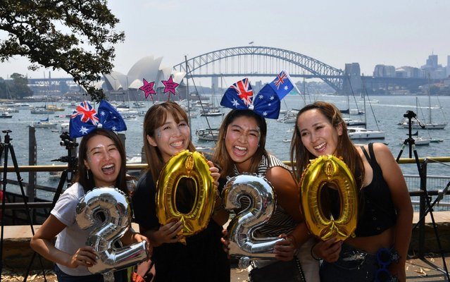 New Year's Eve revellers from Asia with Australian flags and balloons in the shape of the new year 2020 in Sydney, Australia on December 31, 2019. (Photo by Richard Milnes/Rex Features/Shutterstock)