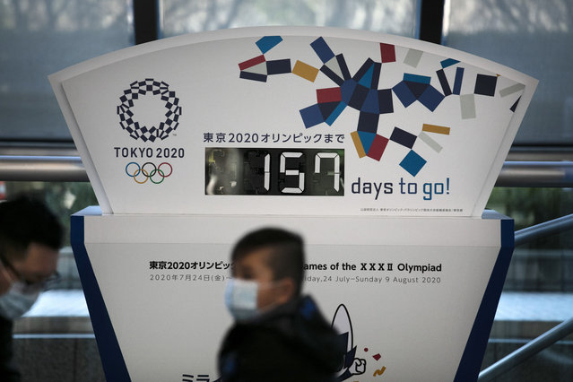 "Two people wearing masks sit in front of a countdown clock for the Tokyo 2020 Olympics Tuesday, February 18, 2020, in Tokyo. Tokyo Olympic organizers said last week there is no ""Plan B"" for the 2020 Games, which open in just over five months and have been jolted by the outbreak of a virus in neighboring China. (Photo by Jae C. Hong/AP Photo)"