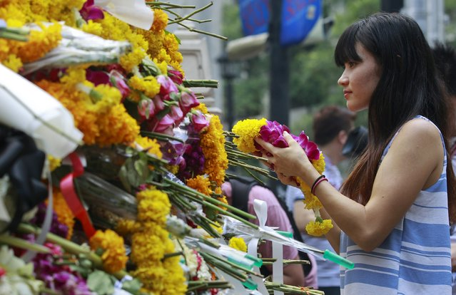 A woman places a wreath at the Erawan shrine, the site of Monday's deadly blast, in central Bangkok, Thailand, August 20, 2015. (Photo by Chaiwat Subprasom/Reuters)