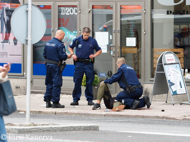 The suspect lies on the ground surrounded by police officers at the Market Square where several people were stabbed, in Turku, Finland August 18, 2017. (Photo by Courtesy Kirsi Kanerva/Reuters)