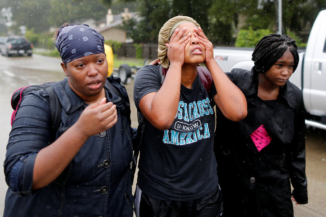 Domenique Scales (C), wipes tears from her face after being rescued from the flood waters in Beaumont Place, Houston, Texas on August 28, 2017. (Photo by Jonathan Bachman/Reuters)