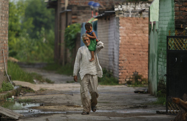 In this Thursday, August 20, 2015, photo, Indian villager Pritam Lal carries his grandson on his shoulder as he walks back to his house, near international border of India and Pakistan in Akhnoor sector, 33 kilometers (21 miles) from Jammu, India. On the face of it these villages in the Jammu region of Indian Kashmir seem idyllic, but over the last two weeks these villages have been witness to an angry exchange of fire and mortar shells between Indian and Pakistani soldiers. (Photo by Channi Anand/AP Photo)