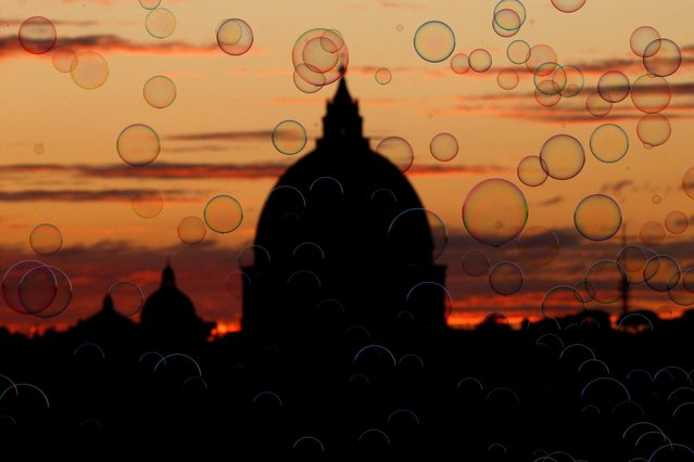 The dome of Saint Peter's Basilica is seen behind soap bubbles created by a street artist (not pictured) from Pincio terrace in Rome, Italy, November 25, 2019. (Photo by Guglielmo Mangiapane/Reuters)
