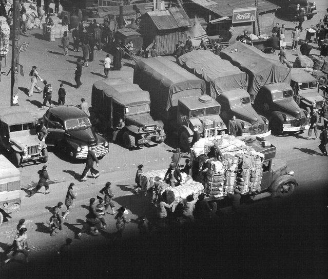 1948年3月,外滩,一群妇女儿童追赶一辆满载棉花的卡车。 (In March 1948, the Bund, a group of women and children to catch up with a truck loaded with cotton)