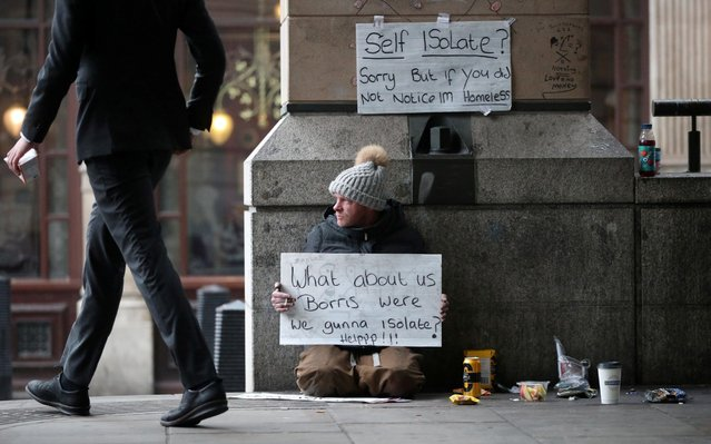 A homeless man holds up a sign outside Westminster underground station as the spread of the coronavirus disease (COVID-19) continues, in London, Britain, March 19, 2020. (Photo by Hannah McKay/Reuters)