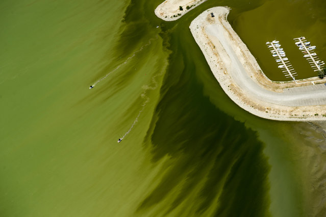 A couple of boats sail through discolored water caused by an algae bloom near the Lindon Marina in Utah Lake in Lindon, Utah. Utah County health officials said at least eight people have fallen ill after interactions in Utah Lake, which has a potentially toxic algae bloom. (Photo by Rick Egan/The Salt Lake Tribune via AP Photo)