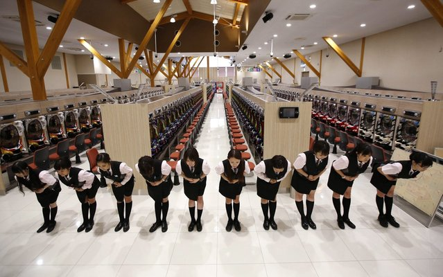 Dynam employees bow in a prescribed way as they receive customer-care training ahead of the grand opening of the company's pachinko parlour in Fukaya, north of Tokyo July 29, 2014. (Photo by Issei Kato/Reuters)