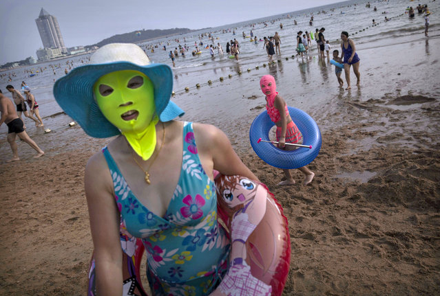 A Chinese woman and her daughter wear face-kinis as they walk on the beach on August 19, 2014 on the Yellow Sea in Qingdao, China. The locally designed mask is worn by many local women to protect them from jellyfish stings, algae and the sun's ultraviolet rays. (Photo by Kevin Frayer/Getty Images)