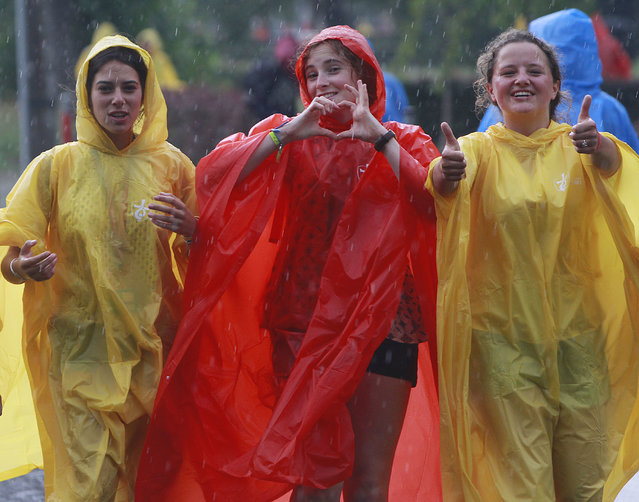 Young women from France are among the dozens of thousands of young people from around the globe walking in thunderstorm to the site of a Catholic Mass in the Blonia green in Krakow, Poland, Tuesday, July 26, 2016 that will officially open the World Youth Day, a major gathering of Catholics that will be joined by Pope Francis on Wednesday. (Photo by Czarek Sokolowski/AP Photo)