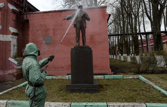 A Russian serviceman wearing a protective suit sprays disinfectant on a monument to the Soviet Union founder Vladimir Lenin while disinfecting an industrial area in Saint Petersburg on April 15, 2020, amid the COVID-19 coronavirus pandemic. (Photo by Olga Maltseva/AFP Photo)