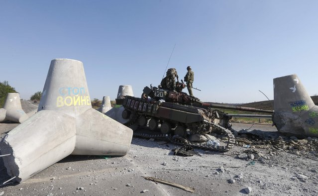 Ukrainian soldiers inspect damaged tank on the outskirts of the southern coastal town of Mariupol September 6, 2014. Russian President Vladimir Putin and Ukraine's President Petro Poroshenko agreed on Saturday in a telephone call that a ceasefire in eastern Ukraine was generally holding but said further steps were needed to make it more durable. (Photo by Vasily Fedosenko/Reuters)