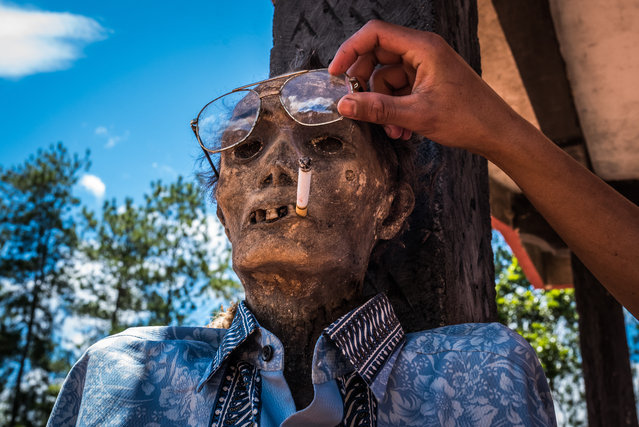 Todeng died in 2009. A young relative of his, Sam, lights him a cigarette and changes his glasses. (Photo by Claudio Sieber Photography/The Guardian)