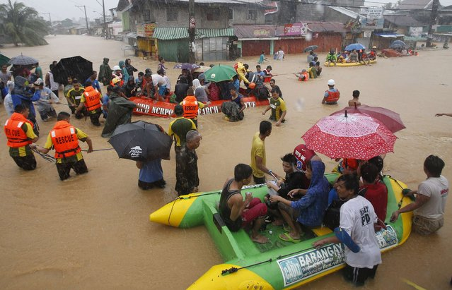 Flood victims are evacuated in rescue boats after their homes were swamped by heavy flooding in Marikina, Metro Manila September 19, 2014. (Photo by Erik De Castro/Reuters)