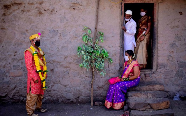 Groom Vitthal Koditkar (L) of Hirpodi village speaks with his bride Vrushali Renuse (R) of Pabe village and family members after their wedding during a government-imposed nationwide lockdown as a preventive measure against the COVID-19 coronavirus, at Pabe village in Pune district on May 12, 2020. (Photo by Sanket Wankhade/AFP Photo)
