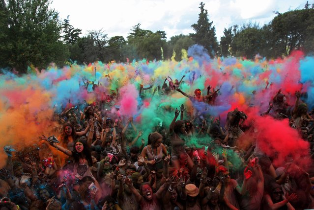 Revelers throw coloured powders in the air during the Holi Festival of Colors, in Lisbon, Sunday, September 14 2014. The festival is fashioned after the Hindu spring festival Holi, which is mainly celebrated in some regions of India and Nepal. (Photo by Francisco Seco/AP Photo)