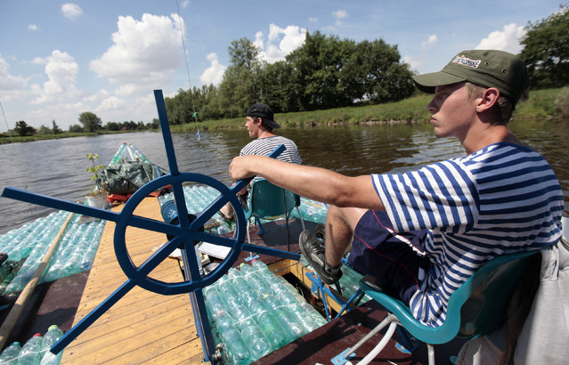 Jakub Bures (R) and Jan Kara pedal their boat, made with plastic bottles, on the Elbe river near Kostelec nad Labem July 15, 2014. (Photo by David W. Cerny/Reuters)