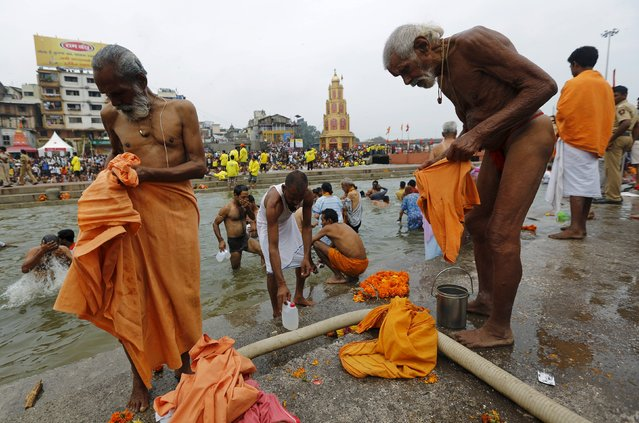 "Sadhus or Hindu holy men get dressed after taking a dip in the waters of Godavari river during the second ""Shahi Snan"" (grand bath) at Kumbh Mela or Pitcher Festival in Nashik, India, September 13, 2015. (Photo by Adnan Abidi/Reuters)"