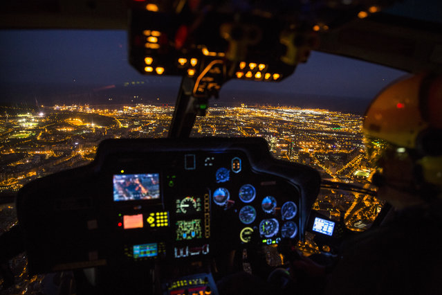 In this Tuesday, September 19, 2017 photo, an officer pilots a Catalan Mossos d'Esquadra helicopter flies over the city of Barcelona, Spain during a patrol. Spain's Catalonia region has its own police force, known locally as the Mossos d'Esquadra, and it has grown from its 18th-century roots into a modern European security agency with about 17,000 members. (Photo by Emilio Morenatti/AP Photo)