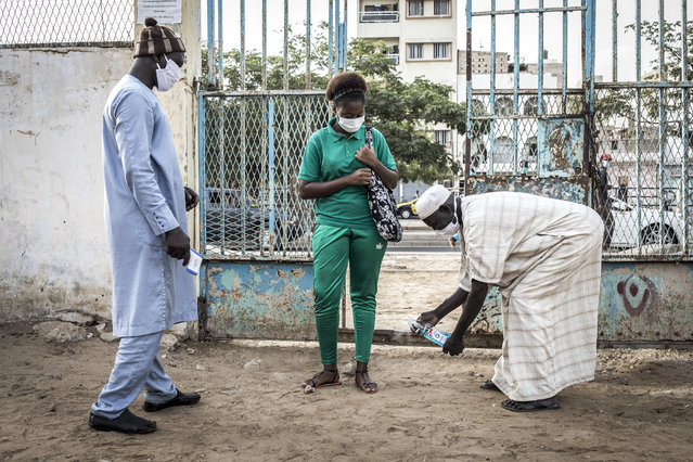 A High School student at the Lycee Blaise Diagne gets her feet disinfected as she arrives for her first day back at school in Dakar on June 25, 2020. Schools have been closed since early March 2020 due to the outbreak of the COVID-19 coronavirus in Senegal. (Photo by John Wessels/AFP Photo)