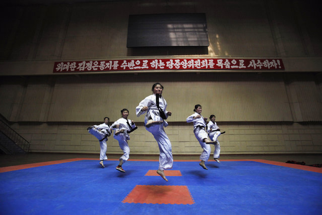 "Girls train in a Taekwondo Hall in Pyongyang April 12, 2012. The banner at background reads ""Let us defend the Party Central Committee headed by the respected comrade Kim Jong-un, at the cost of our lives!"". (Photo by Bobby Yip/Reuters)"