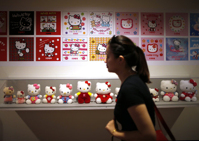 """A woman walks past a display case at the """"Hello! Exploring the Supercute World of Hello Kitty"""" museum exhibit in honor of Hello Kitty's 40th anniversary, at the Japanese American National Museum in Los Angeles, California October 10, 2014. (Photo by Lucy Nicholson/Reuters)"""