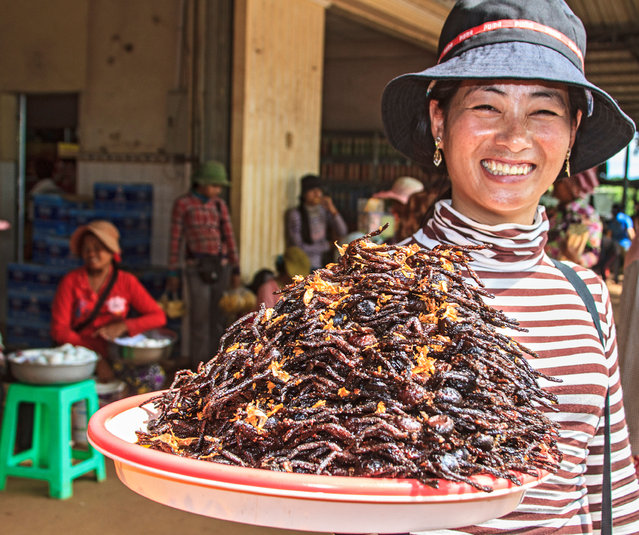 """Woman with a mound of breaded and deep fried tarantulas for sale at Skuon, Cambodia, known locally as """"Spiderville"""". (Photo by Alamy Stock Photo)"""