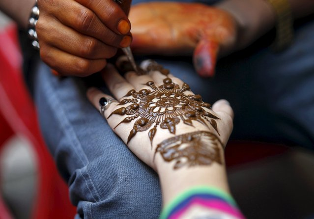 A girl gets her hand decorated with henna paste at a marketplace ahead of the Eid al-Adha festival in Srinagar September 23, 2015. Eid al-Adha in Kashmir falls on Friday. (Photo by Danish Ismail/Reuters)