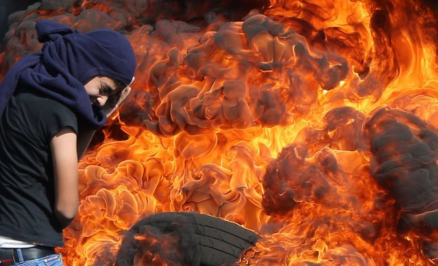 A Palestinian protester protects his face as he stands in front of burning tires during a demonstration against the expropriation of Palestinian land by Israel in the village of Kafr Qaddum, near Nablus in the occupied West Bank, on October 26, 2014. Israeli-Palestinian talks on a lasting Gaza truce are to resume after mid-November, instead of October 27, 2014 as initially planned, the chief Palestinian negotiator Azzam al-Ahmad told AFP. (Photo by Jaafar Ashtiyeh/AFP Photo)