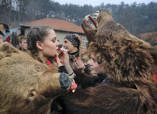 In this Saturday, December 30, 2017 picture Raluca Atrejei, right, helps Roxana Stan, apply lipstick as they get ready for an annual bear parade in Comanesti, Romania. (Photo by Vadim Ghirda/AP Photo)