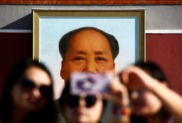 People take pictures on Tiananmen Square as the portrait of China's late Chairman Mao Zedong is seen in the background in Beijing, China, on the 40th anniversary of his death September 9, 2016. (Photo by Thomas Peter/Reuters)