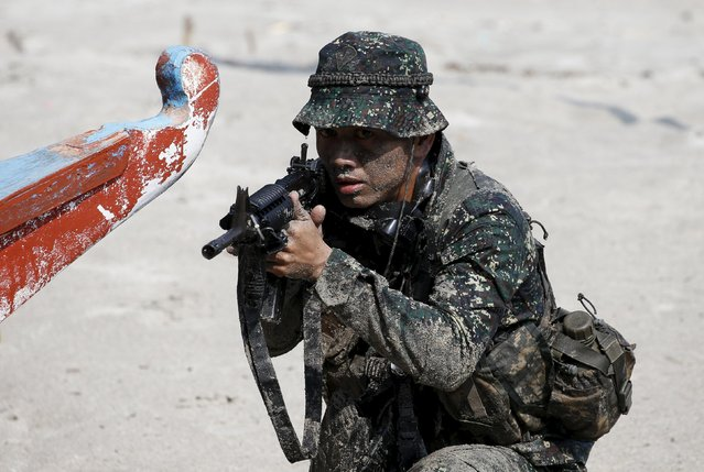 A Philippine marine troop takes up position during a mock beach assault exercise with U.S. marines in joint drills aimed at enhancing cooperation between the allies in Ternate, Cavite October 8, 2015. (Photo by Erik De Castro/Reuters)