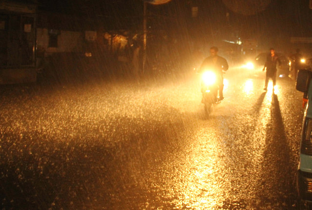 People make their way on a road during monsoon rains in Hyderabad, Pakistan, 06 august 2020. (Photo by Nadeem Khawer/EPA/EFE)