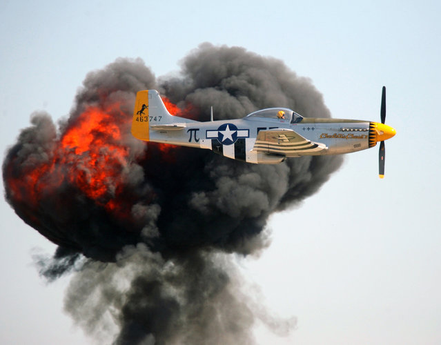 "A P-51 Mustang named ""Charlotte's Chariot"" from the Southern Heritage Air Foundation flies past a cloud of smoke and fire from a nearby battle reenactment during the Wings Over Houston Airshow in Houston, on Saturday, November 1, 2014. Battle reenactments are part of the yearly show held at Ellington Airport. (Photo by Kar Hlava/AP Photo/Bay Area Citizen)"