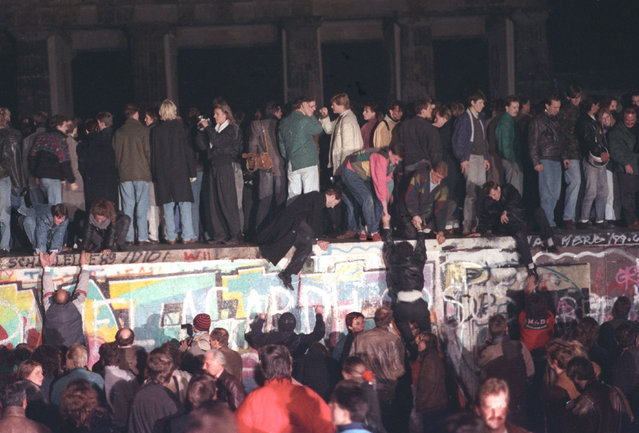 West Berlin citizens continue their vigil atop the Berlin Wall in front of the Brandenburg Gate, November 10, 1989. (Photo by Andree Kaiser/Reuters)